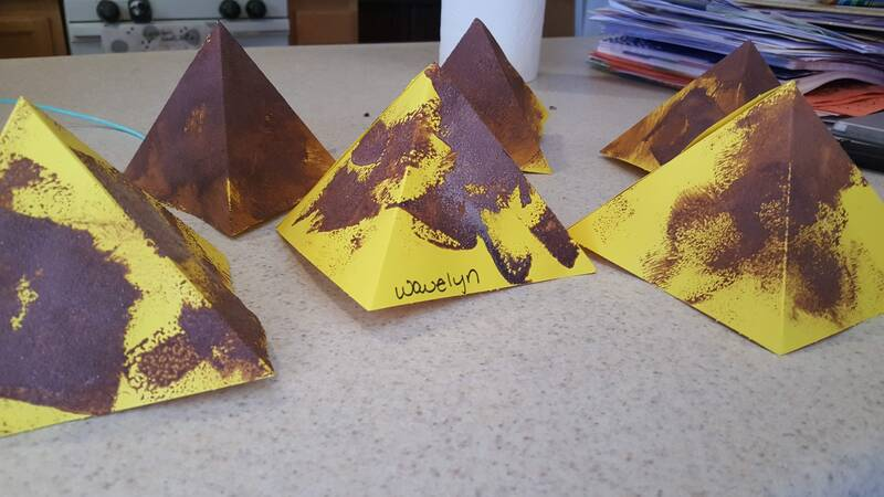Children stamping pyramids with sand and paint